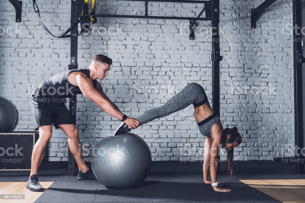trainer helping woman work out royalty-free stock photo