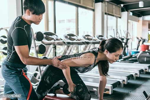 Personal trainer helps his female client to do one-arm dumbbell row exercise in modern gym.