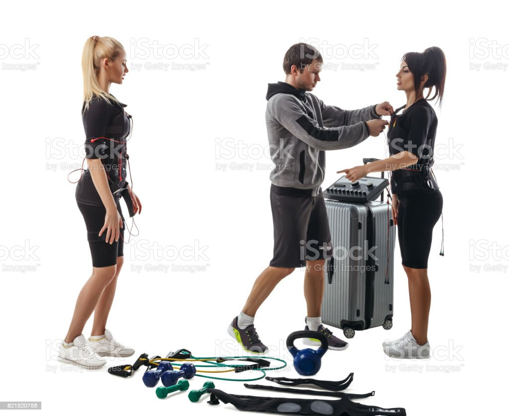 Trainer helps women to set EMS suit stock photo