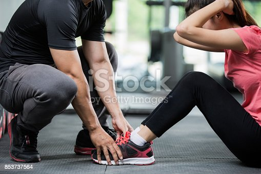 istock Trainer holding a woman in the leg exercise by Sid-ups. 853737564