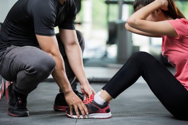 entrenador con una mujer en la pierna del ejercicio por sid-ups. - entrenador personal fotografías e imágenes de stock