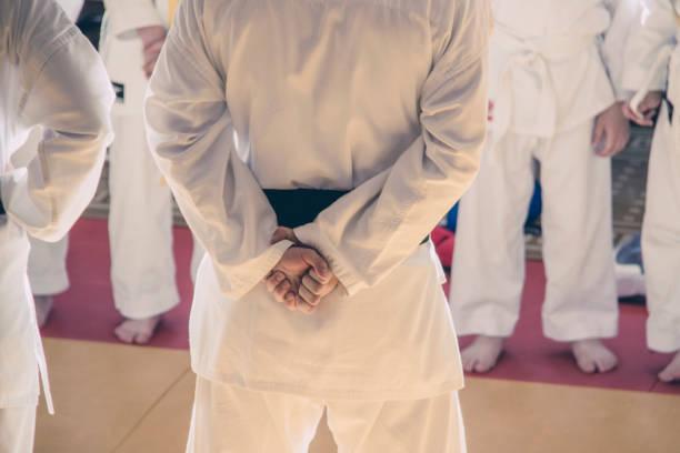 un entrenador en un kimono está parado con la espalda con sus brazos cruzados en la espalda delante de sus alumnos. - kárate fotografías e imágenes de stock