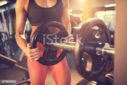 670937518istockphoto Trainer in gym putting weights on machine, concept 873830032
