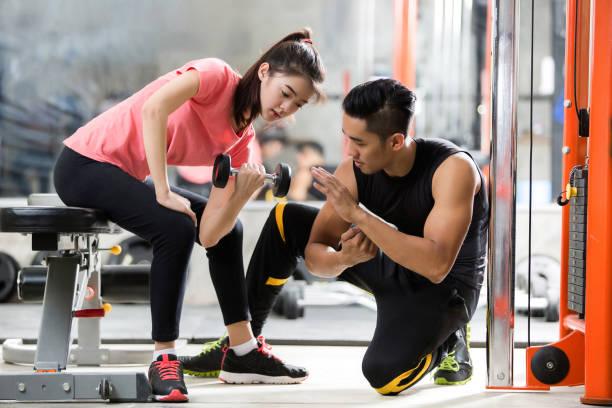 トレーナーの男性は、ダンベルを持ち上げてアジアの女性を教えています。方法で彼らはジムで運動します。 ストックフォト