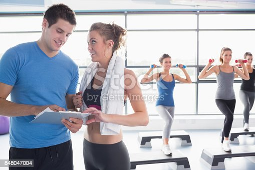 Trainer presenting timetable while aerobics class lifting weights in gym