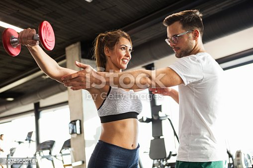 istock Trainer showing exercise with dumbbells 1078955214