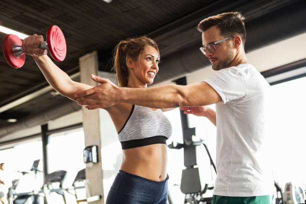 trainer tonen oefening met halters - personal trainer stockfoto's en -beelden