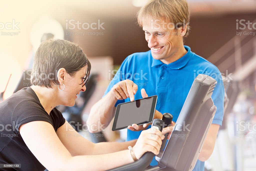 Trainer showing results of training on tablet PC to woman stock photo