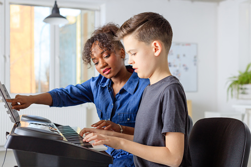 Trainer Showing Sheet To Student And Playing Piano Stock Photo - Download Image Now