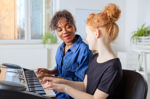 Trainer Singing With Student While Playing Piano Stock Photo - Download Image Now