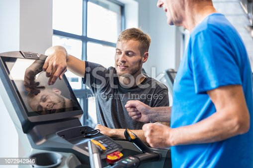 Instructor explaining how to use treadmill to senior man at the gym. Trainer supervising old man on treadmill and explaining adjustments at rehab gym.