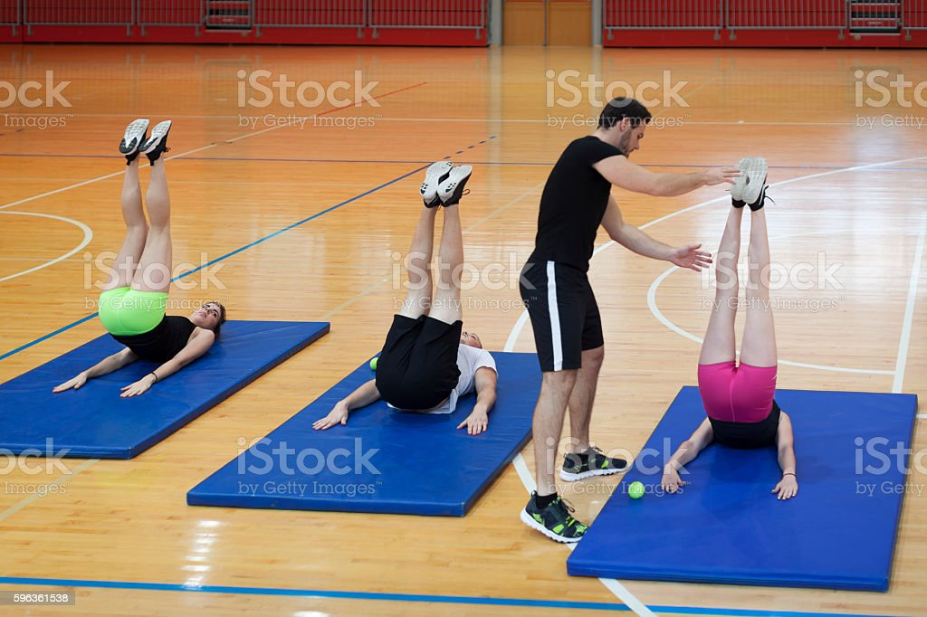 Trainer Teach Young Athletes how to do Exercises in Gym royalty-free stock photo