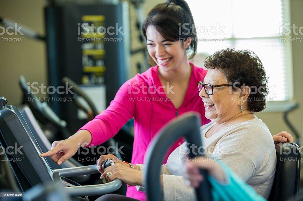 Enseña Senior Instructor cliente de cómo usar la máquina en el gimnasio - foto de stock