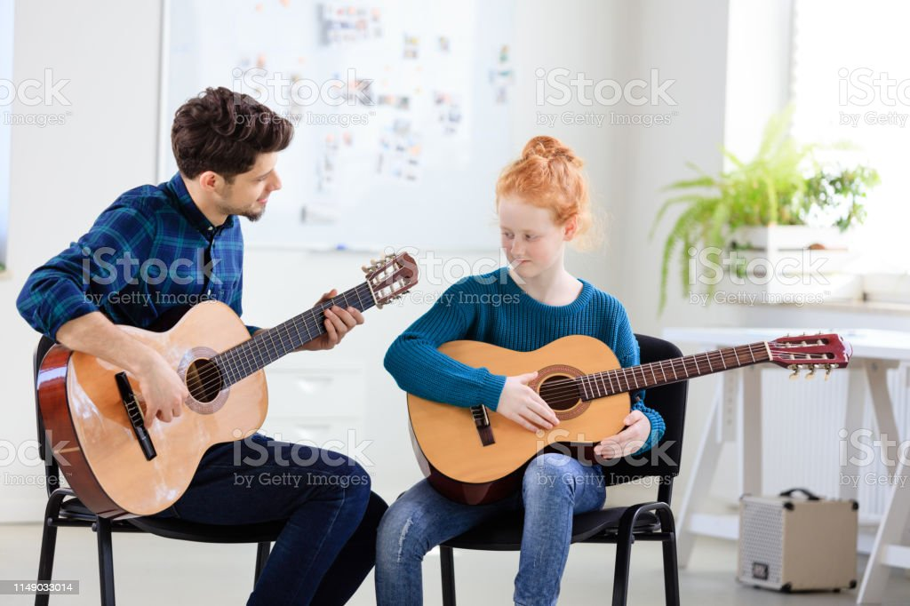Trainer teaching girl plucking string instrument Male trainer teaching girl plucking guitar at classroom. Student is practicing string instrument at conservatory. They are in training class. 12-13 Years Stock Photo