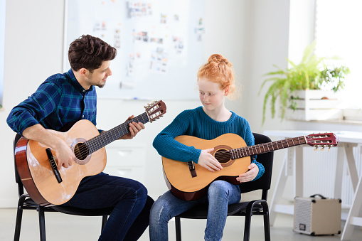 Trainer Teaching Girl Plucking String Instrument Stock Photo - Download Image Now