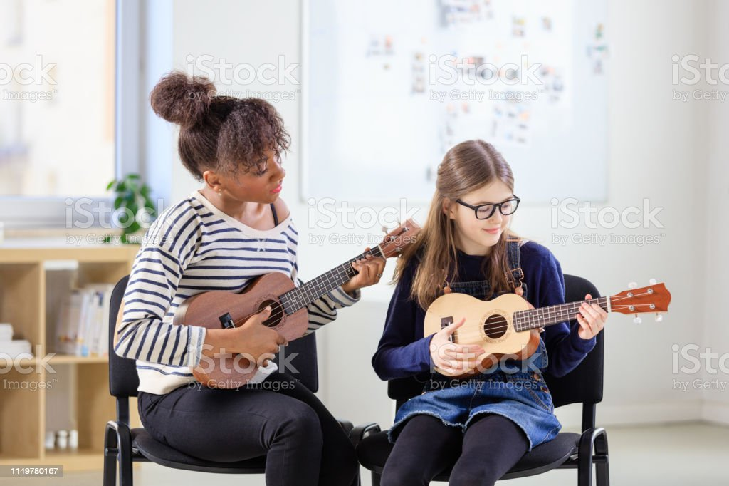 Trainer teaching girl plucking ukulele in class Music trainer teaching girl plucking ukulele at classroom. Pre-adolescent female is practicing string instrument at conservatory. They are sitting on chair in training class. 10-11 Years Stock Photo