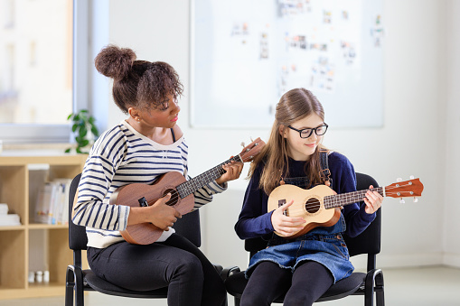 Trainer Teaching Girl Plucking Ukulele In Class Stock Photo - Download Image Now