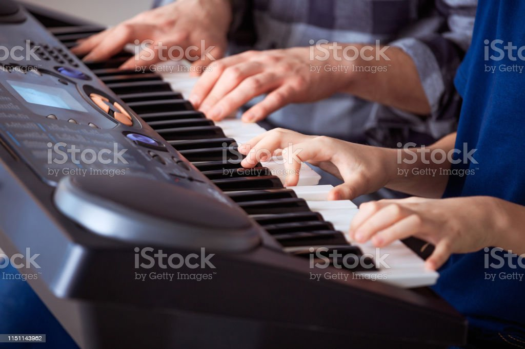 Trainer teaching piano to boy in class Midsection of male teacher teaching piano to male student. Pre-adolescent boy is learning in music class. They are at conservatory. 12-13 Years Stock Photo
