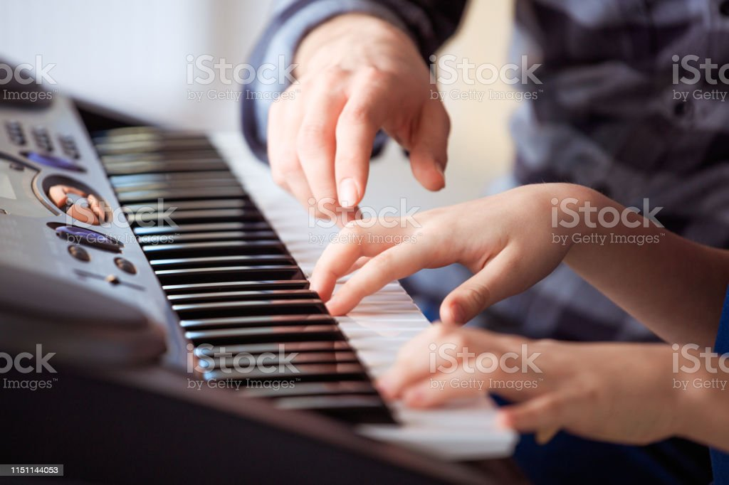 Trainer teaching piano to boy in class Male teacher teaching piano to male student. Pre-adolescent boy is learning music in class. They are practicing at conservatory. 12-13 Years Stock Photo