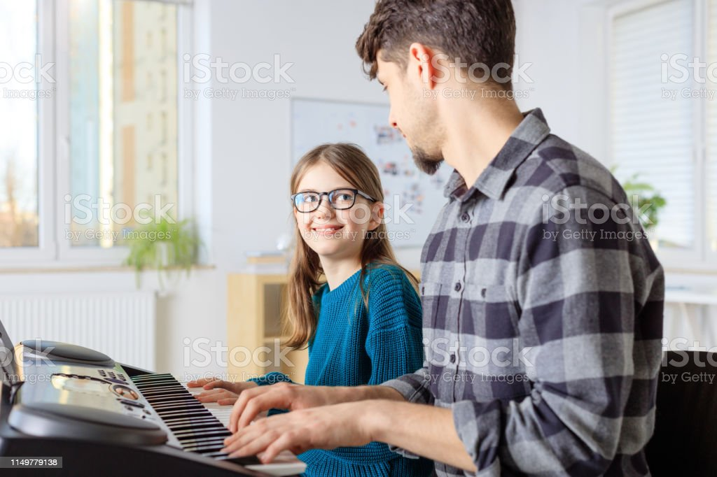 Trainer teaching piano to girl in class Male teacher playing piano with pre-adolescent girl. Student is learning music from instructor in training class. They are at conservatory. 10-11 Years Stock Photo