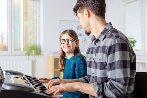 Trainer Teaching Piano To Girl In Class Stock Photo - Download Image Now