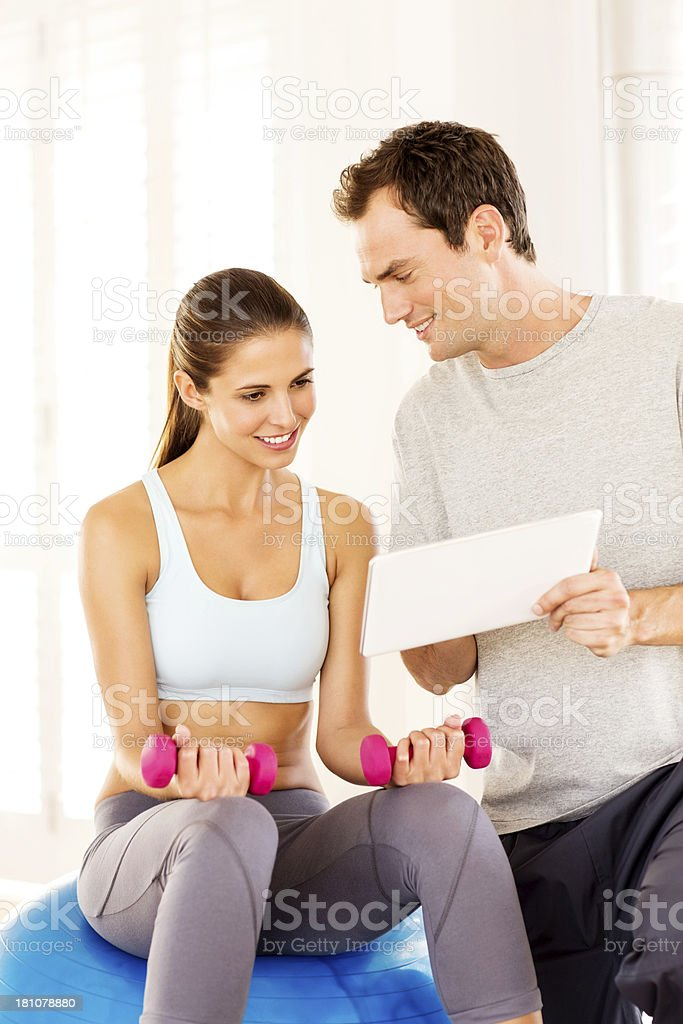 Trainer With Digital Tablet Explaining Exercise Plan To Woman royalty-free stock photo