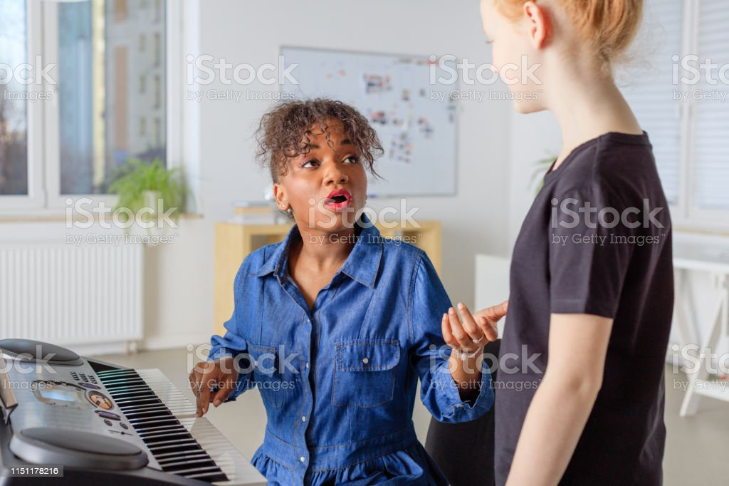 Trainer with piano teaching girl to sing in class Mid adult instructor playing piano while singing with student. Teacher is assisting pre-adolescent girl at music class. They are at education building. 12-13 Years Stock Photo
