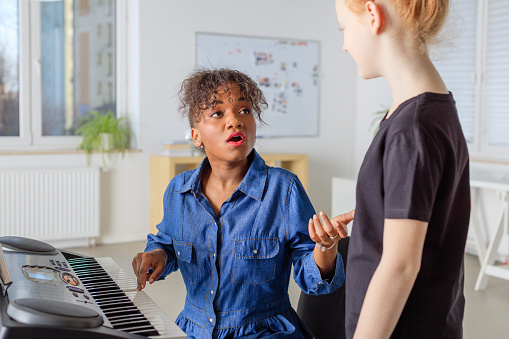 Trainer With Piano Teaching Girl To Sing In Class Stock Photo - Download Image Now