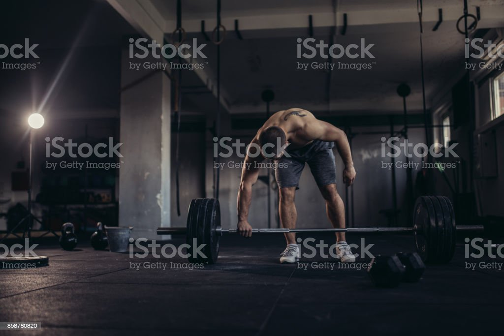 One man, handsome and strong, doing weightlifting training in the gym.