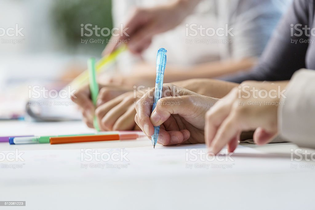 Training for women Group of women attending a training, working together. Close up of hands holding pens. Adult Stock Photo