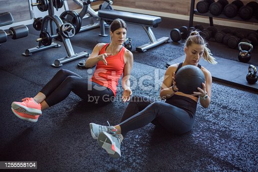 Young women exercising together with medicine ball in the gym.