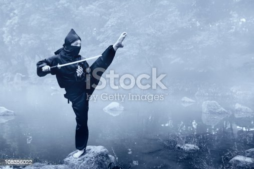 Ninja woman on a foggy lakeside in early morning.