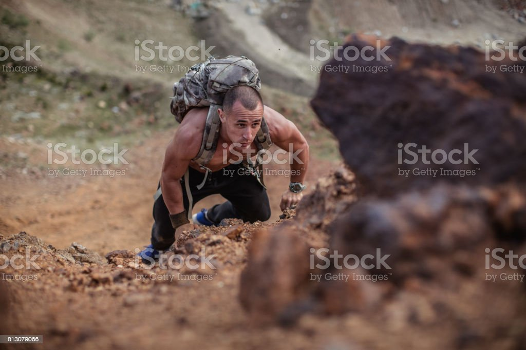 One man, climbing up the hill, shirtless and very fit, wearing a...