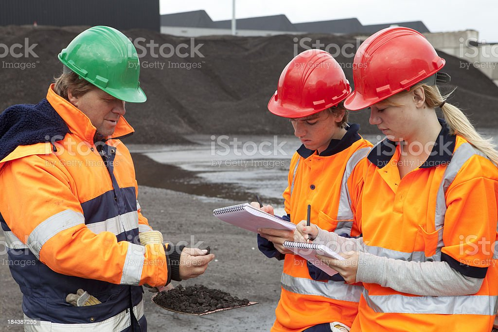 Training outdoors. Trainee making notes. Learning about asphalt. stock photo