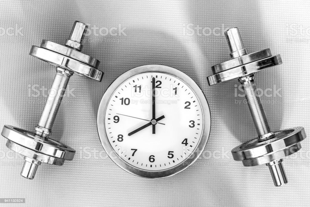Training: Silver dumbbells lying next to a round clock, shows 8 o'clock stock photo