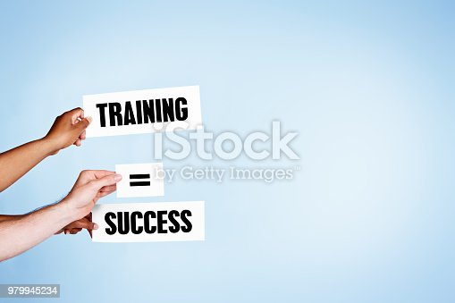 Three hands hold up signs reading Training = Success