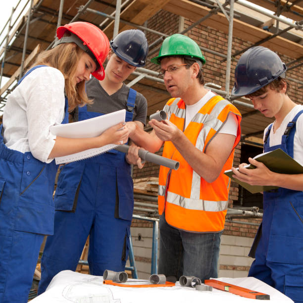 Training to be a plumber. Trainee making notes Vocational student learns for plumber from an experienced instructor.  If you want more images with a trainee please click here. pipefitter stock pictures, royalty-free photos & images