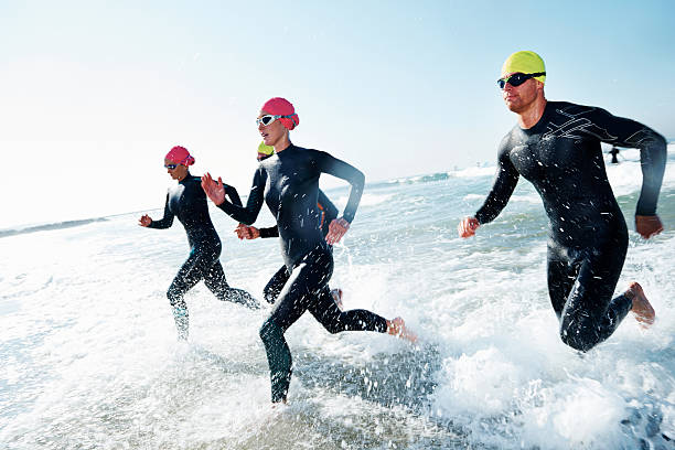 Training to win A group of athletes competing in a triathlon wetsuit stock pictures, royalty-free photos & images