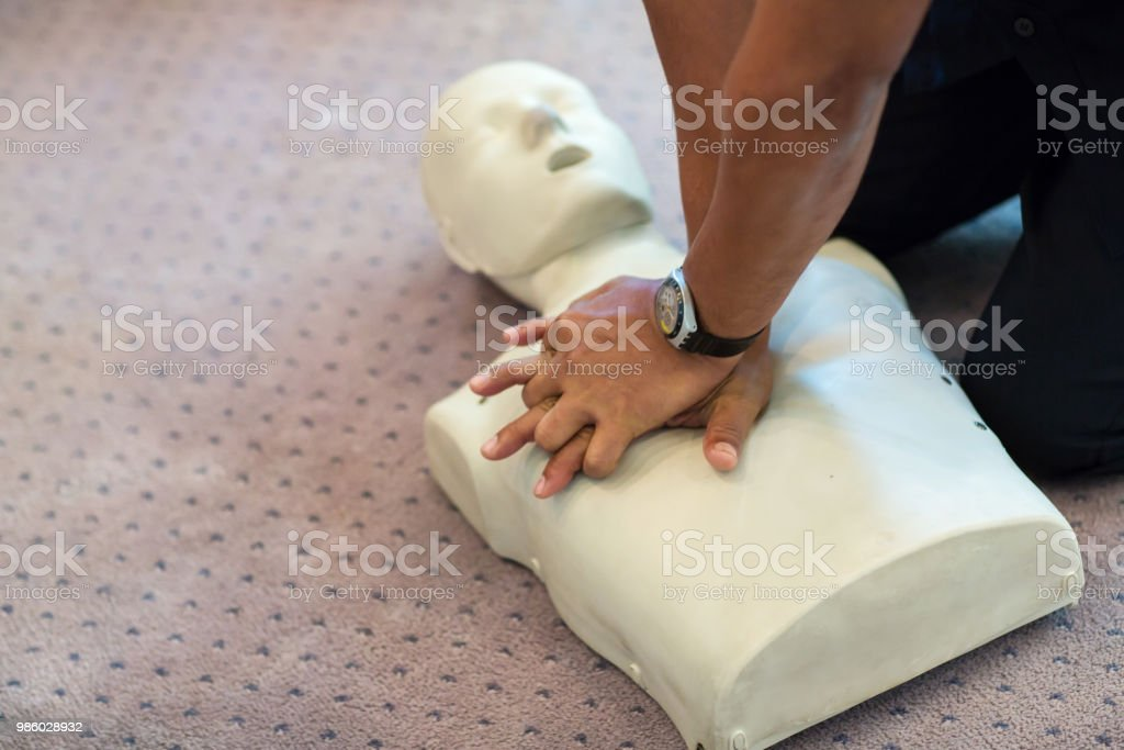 CPR training using and an AED and bag mask valve on an adult training manikin. stock photo