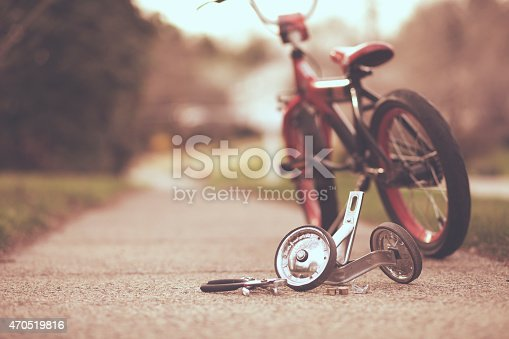 Set of training wheels taken off of a child's bicycle with some tools laying on the ground.