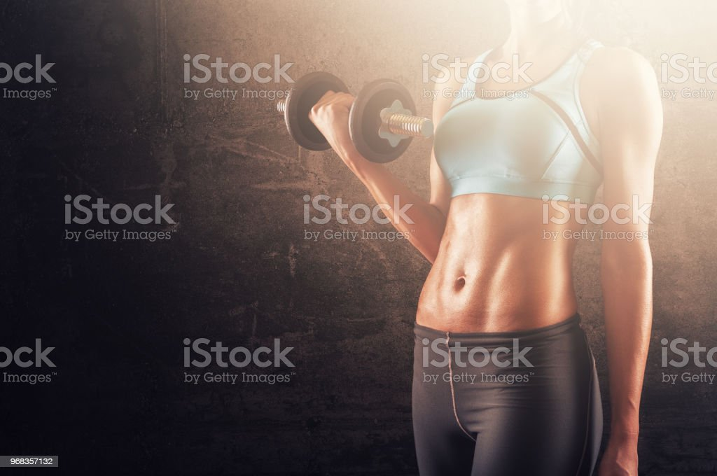 Training woman with dumbbells in her hand stock photo