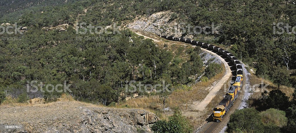 Trainload of black coal grinds downhill towards port royalty-free stock photo