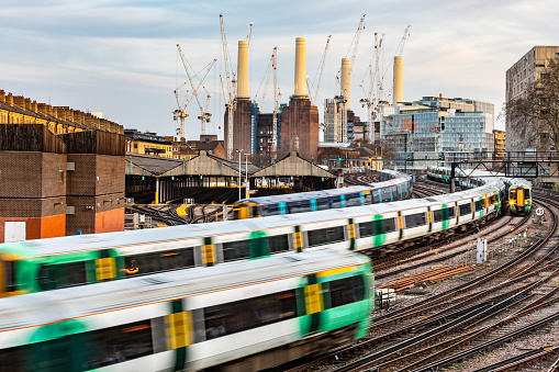 Trains on the tracks and power station in London. Blurred trains leaving and arriving next a busy station. City background with buildings and construction in progress. Travel and transport concepts