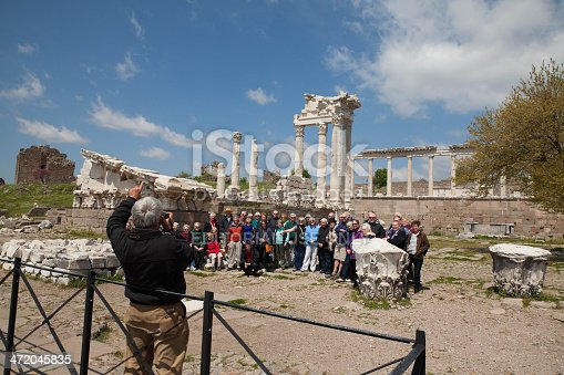 İzmir, Turkey - April 17, 2013: Tourists visiting Acropolis, Bergama (Pergamon city) one of capital of ancient Greek. The Asklepion in Pergamon was a healing in the ancient Greece as important as its counterparts in Epidaurus and Kos.The first temple of Asclepius in Pergamon was built in the first of the 4th century B.C. A group of people visiting listening the tour guide beside the columns in the image.
