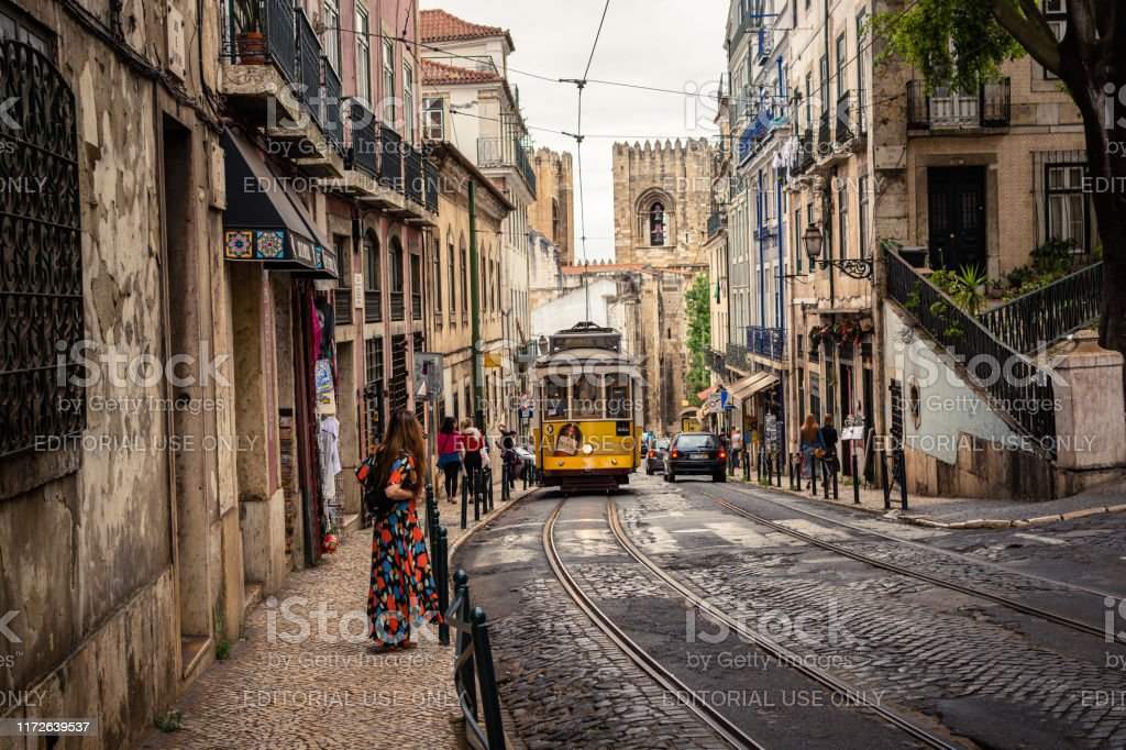 Tram 28 transports tourists through Alfama district in Lisbon, Portugal - Royalty-free Adult Stock Photo