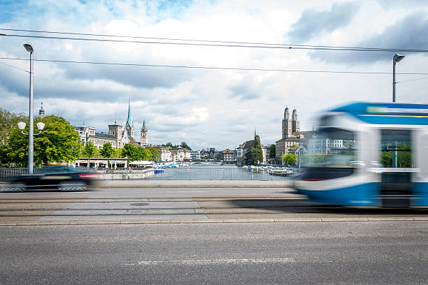 Tram and Car on a Bridge of Zurich, Switzerland A tram passing by the city center of Zurich in Switzerland. The tram is blurred due to motion and long exposure. zurich stock pictures, royalty-free photos & images