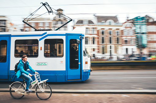 Amsterdam, Netherlands - April 17, 2018: Street scene from Amsterdam (near central station) with moving tram and cyclist riding by. Motion blurred.