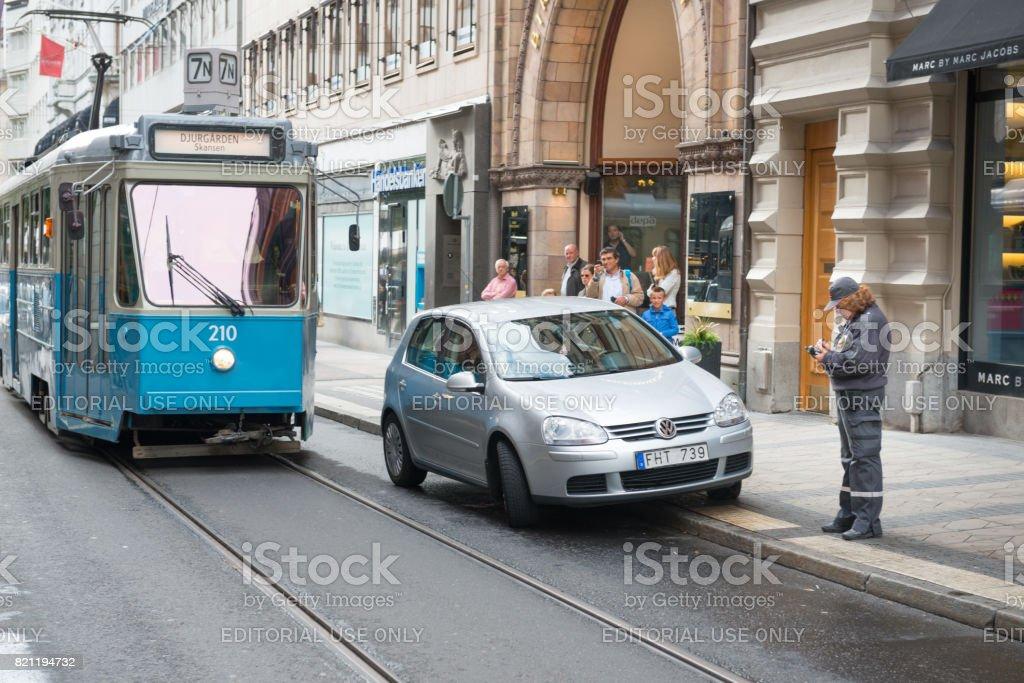 Eléctrico e o carro estacionado em apuros - foto de acervo
