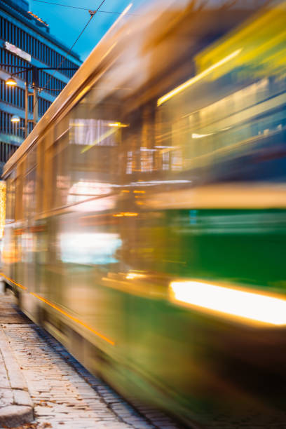 tram departs in motion blur from a stop on mannerheim avenue in helsinki. night view of mannerheim avenue in kluuvi district in evening or night illumination - stop motion stock photos and pictures