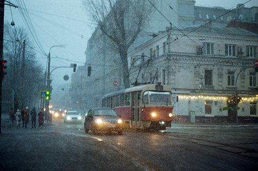 Tram in Kyiv while snowing at the evening. Camera film, vintage